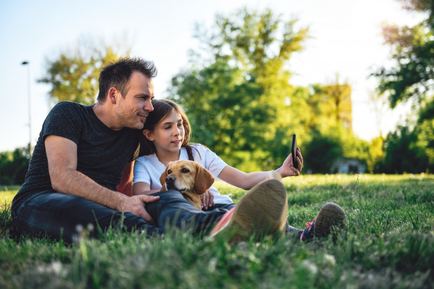 father-daughter-relaxing-park-with-dog_137573-1223
