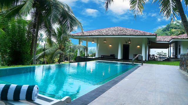 Podlhovastý bazén pred malým bielym domom.jpg