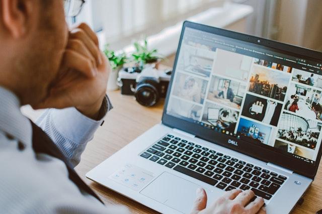 Muž v košeli a dioptrických okuliaroch pracuje na notebooku