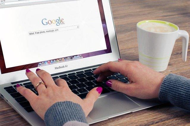 Žena s nalakovanými nechtami píše na notebooku, kde má zapnutý Google